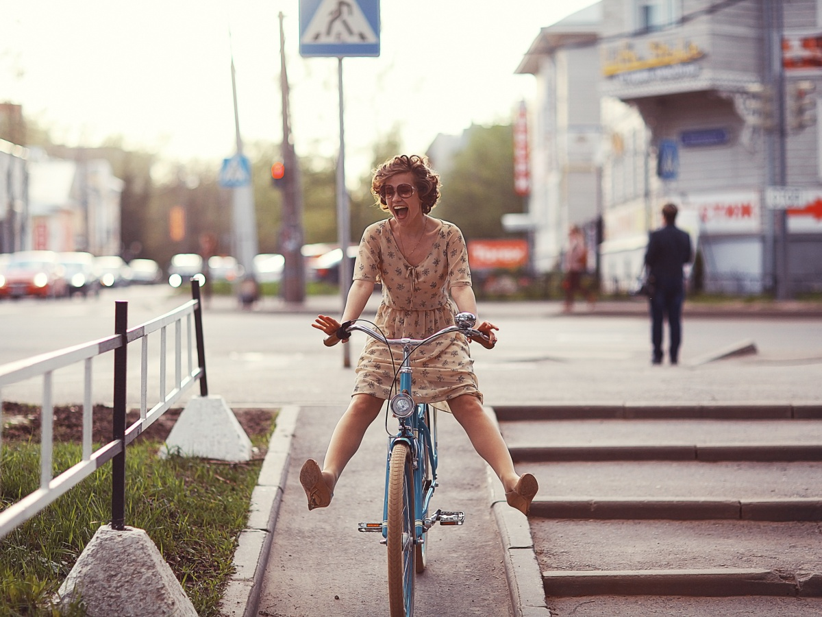 cheerful girl on a bicycle movement